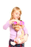 Little girl combing hair her doll on a white background Royalty Free Stock Image