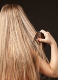 Little girl combing her beautiful long hair Stock Photo