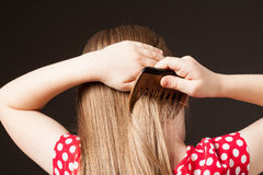 Little girl combing her beautiful long hair Stock Photo