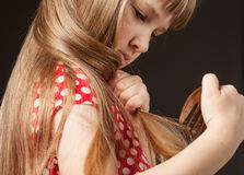 Little girl combing her beautiful long hair Royalty Free Stock Photography