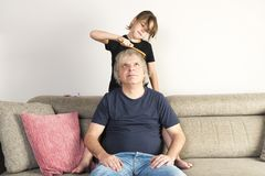 Little girl combing her dad at home. Little girl combing her dad on the couch at home royalty free stock photo