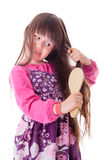 Little girl combing her frizzy hair Royalty Free Stock Image
