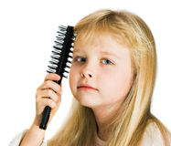 Little girl combing her hair Royalty Free Stock Images