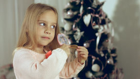 Little girl combing her hair standing near the Christmas tree Royalty Free Stock Photo