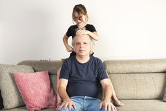 Little girl combing and making pigtails her dad at home. Little girl combing and making pigtails or braids to her dad on the couch at home stock image
