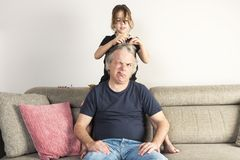 Little girl combing and making pigtails her dad at home. Little girl combing and making pigtails or braids to her dad with a surprised face on the couch at home royalty free stock photo