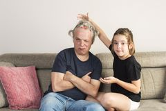 Little girl combing and making pigtails her dad at home. Little girl combing and making pigtails or braids with colored gummies and ties to her dad on the couch royalty free stock photos