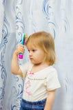 The little girl combs hair a hairbrush. The little girl brushes the hair with a hairbrush Stock Image
