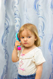 The little girl combs hair a hairbrush. The little girl brushes the hair with a hairbrush Royalty Free Stock Photos