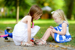 Little girl comforting her sister after she fell while riding her scooter Stock Photography