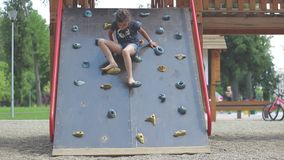 Little girl is coming down on climbing wall in the public playground. Little barefoot girl is coming down on climbing wall in the public playground stock video footage