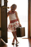 Little girl coming home from traveling trip. Little girl opening up front door,wearing skirt and holding suitcase coming home Royalty Free Stock Photo