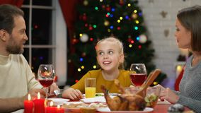 Little girl communicating with parents at Christmas dinner, family celebration. Stock footage stock footage