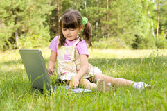 Little girl with computer. The small nice girl works on a computer, sits on a beautiful green lawn, Smile . Profile Adobe RGB (1998 Royalty Free Stock Photos