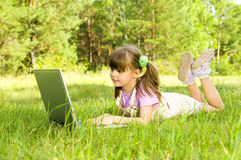 Little girl with computer. The small nice girl works on a computer, lays on a beautiful green lawn, Smile . Profile Adobe RGB (1998 Stock Photo