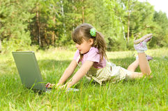 Little girl with computer. The small nice girl works on a computer, lays on a beautiful green lawn, Smile . Profile Adobe RGB (1998 Royalty Free Stock Image