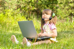 Little girl with computer. The small nice girl works on a computer, lays on a beautiful green lawn, Smile . Profile Adobe RGB (1998 Royalty Free Stock Photography
