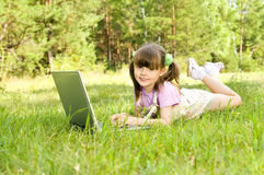 Little girl with computer. The small nice girl works on a computer, lays on a beautiful green lawn, Smile . Profile Adobe RGB (1998 Stock Image