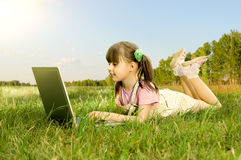 Little girl with computer. The small nice girl works on a computer, lie on a beautiful green lawn, Smile stock images