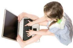 Little girl with computer. The  little girl Plays on computer on white background isolated Royalty Free Stock Photo