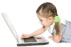 Little girl with computer. The  little girl Plays on computer on white background isolated close up Royalty Free Stock Photo