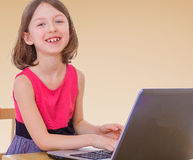 Little girl at the computer. Cheerful little girl sits at a laptop.The concept of development of the child, the child's upbringing Stock Photo