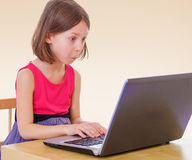 Little girl at the computer. The little girl presses keys laptop.The concept of development of the child, the child's upbringing Royalty Free Stock Photo