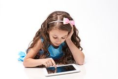 Little girl. Computer tablet. Modern technologies. White background. Brown hair royalty free stock photos