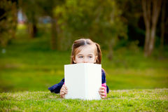 A little girl comtemplating her reading outside. Royalty Free Stock Images
