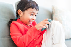 Little girl concentrate on using mobile phone. Asian mixed little girl at home Stock Photography