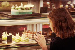 Little girl in confectionary shop looking at the display. Sweet. Little girl  confectionary shop touching the display. Sweet treats variety. Small business and Royalty Free Stock Photography