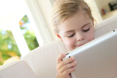 Little girl connected to internet using a tablet Stock Photos
