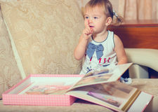 The little girl is considering an album of photographs Royalty Free Stock Image