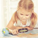 Little girl considering a world map with a magnifying glass Royalty Free Stock Photography