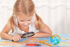 Little girl considering a world map with a magnifying glass Stock Photo