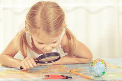 Little girl considering a world map with a magnifying glass Stock Photos