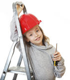 Girl in the construction helmet with a screwdriver. Royalty Free Stock Photography