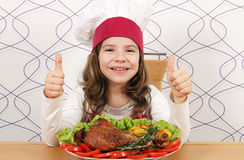 Little girl cook with big drumstick and thumbs up. Happy little girl cook with big drumstick and thumbs up royalty free stock photos