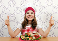 Little girl cook with burritos and thumbs up Royalty Free Stock Photography
