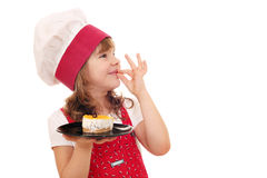 Little girl cook with cake and ok hand sign Stock Images