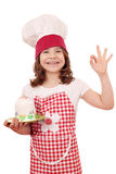 Little girl cook with cake and ok hand sign Royalty Free Stock Photos