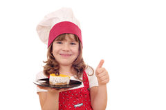 Little girl cook with cake and thumb up Stock Photos