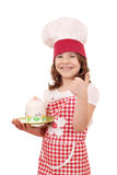 Little girl cook with cake and thumb up Royalty Free Stock Photos