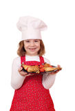 Little girl cook with chicken drumstick on plate Royalty Free Stock Photography