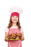 Little girl cook with chicken wings on plate Royalty Free Stock Images