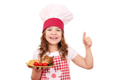 Little girl cook with chicken wings and thumb up Royalty Free Stock Image