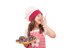 Little girl cook with chocolate donuts and ok hand sign Royalty Free Stock Image