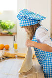 Little girl in a cook clothes holds in a hands a circle of dough on a table Royalty Free Stock Photography