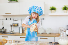 Little girl in a cook clothes kneads a dough in a hands on a kitchen Royalty Free Stock Image