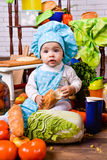 Little girl in the cook clothes with loaf of bread Stock Image